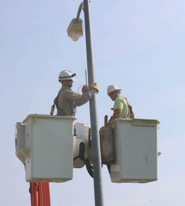 Seth Marek and Joe Brinkman, OPPD line technicians, mount equipment for testing.