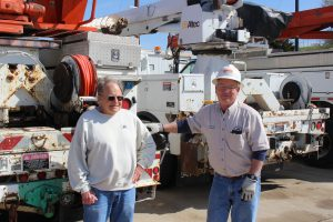 Retired OPPD line workers pose in front of OPPD utility trucks