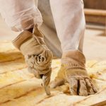 A person cuts insulation prior to insulation in a home. Courtesy 123rf.com