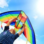 15597532 – llittle boy flies a kite into the blue sky