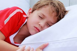 15600175 – cute 7 years old boy sleeping on white pillow in summer cafe