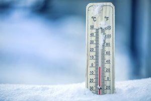Thermometer on snow shows low temperatures – zero. Low temperatu